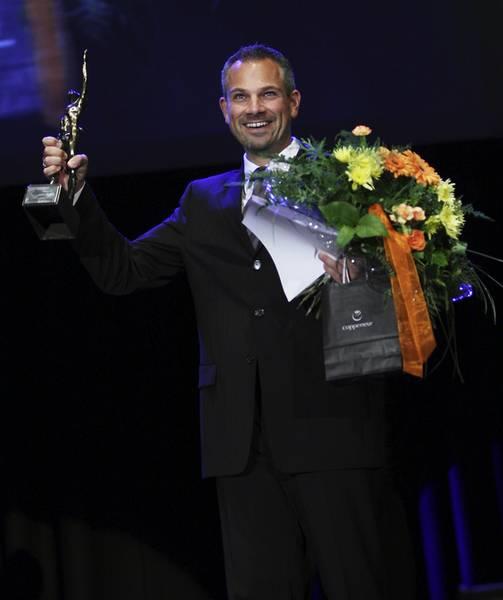 Grosser Preis des Mittelstands Markus Baumann mit Pokal und Blumenstrauß